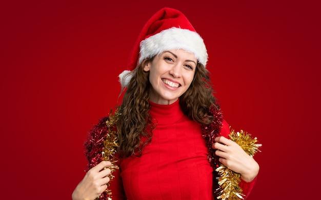 Девушка с шляпой рождества над изолированной красной стеной Premium Фотографии
