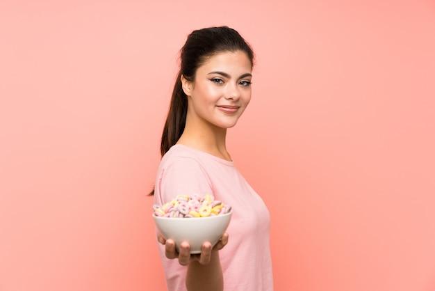 分離のピンクの壁に朝食用シリアルを持つティーンエイジャーの女の子 Premium写真
