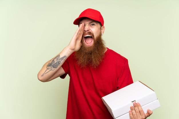 口を大きく開けて叫んで分離の緑の背景の上の長いひげを持つ配達人 Premium写真