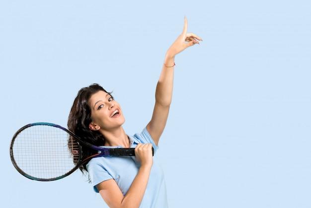 素晴らしいアイデアを指している若いテニスプレーヤー女性 Premium写真