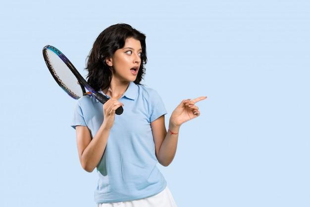 若いテニスプレーヤーの女性が驚いて、ポインティング側 Premium写真