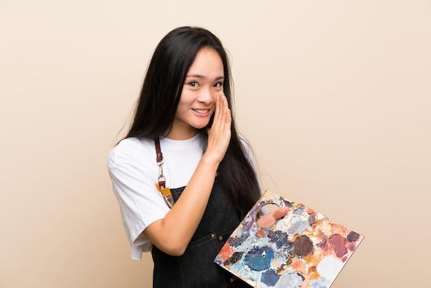 Художник подростка азиатская девушка шепча что-то Premium Фотографии