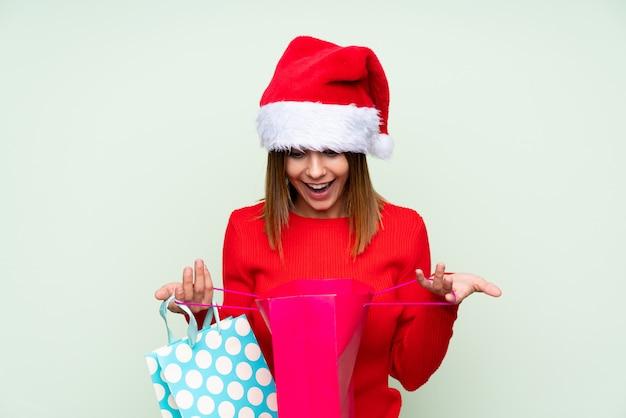 クリスマス帽子と分離された緑の上の買い物袋を持つ少女 Premium写真