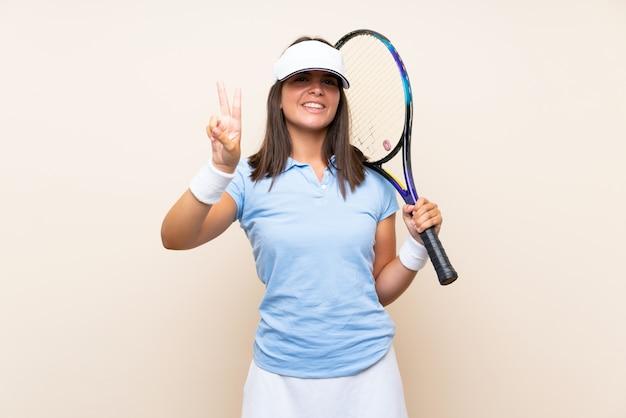 笑顔と勝利のサインを示す孤立した壁の上のテニスの若い女性 Premium写真