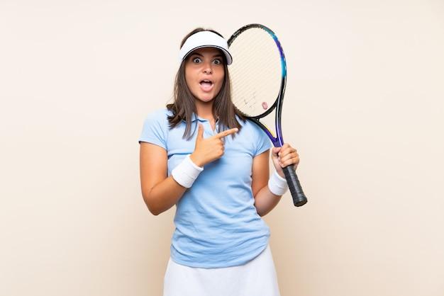 孤立した壁にテニスをしている若い女性が驚いて、側を指す Premium写真