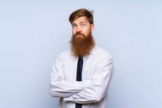アイデアを考えて孤立した壁の上の長いひげを持ったビジネスマン Premium写真