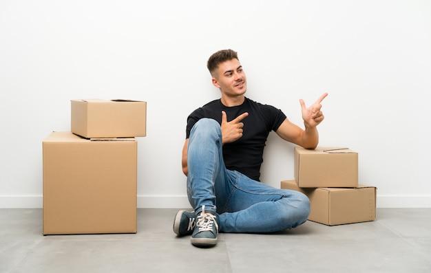 ハンサムな若い男が側に指を指しているボックスの間で新しい家に移動 Premium写真