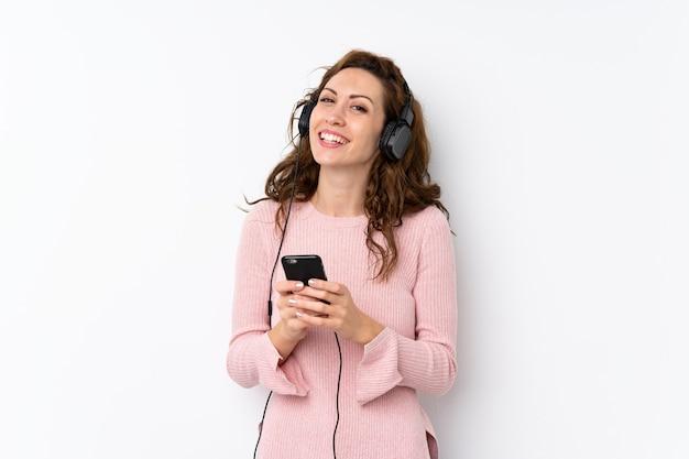 Молодая красивая женщина, используя мобильный телефон с наушниками Premium Фотографии