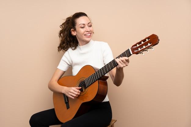 Молодая женщина с гитарой Premium Фотографии