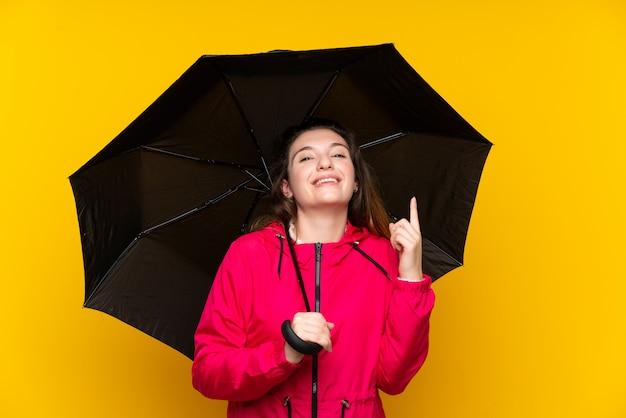 Молодая брюнетка девушка держит зонтик, указывая на отличную идею Premium Фотографии