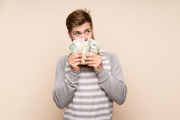 Рыжий мужчина с длинной бородой, принимая много денег Premium Фотографии
