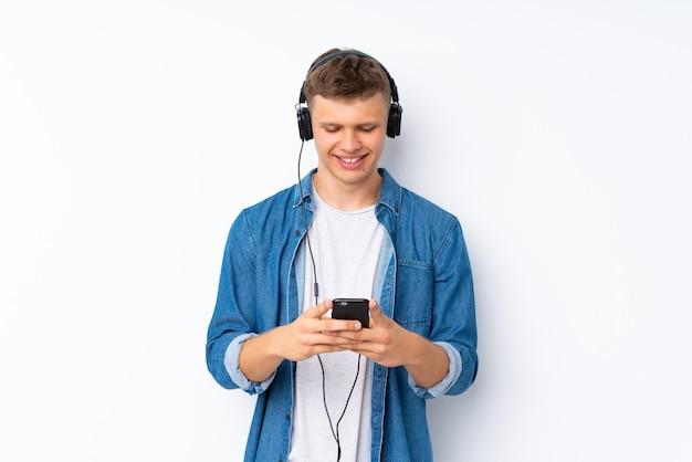 Молодой красавец над белым, используя мобильный телефон с наушниками Premium Фотографии