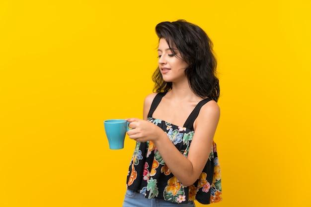 熱い一杯のコーヒーを保持している孤立した黄色の背景の上の若い女性 Premium写真