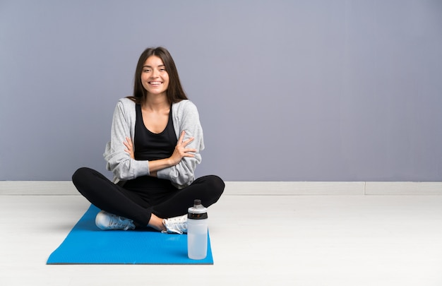 マット笑って床に座っている若いスポーツ女性 Premium写真