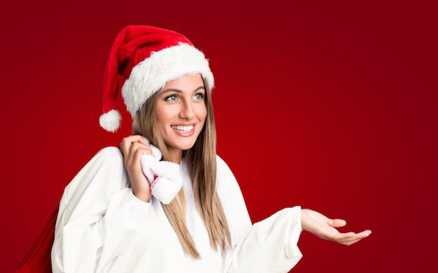 В рождественские каникулы молодая блондинка поднимает сумку, полную подарков, на изолированной красной стене Premium Фотографии