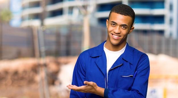 建設現場に向かって笑顔を見ながらアイデアを提示する若いアフロアメリカンワーカー男 Premium写真