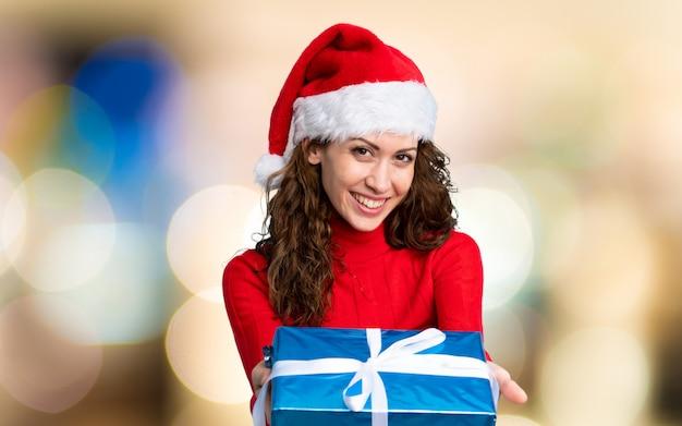 Девушка в новогодней шапке на несосредоточенном фоне Premium Фотографии