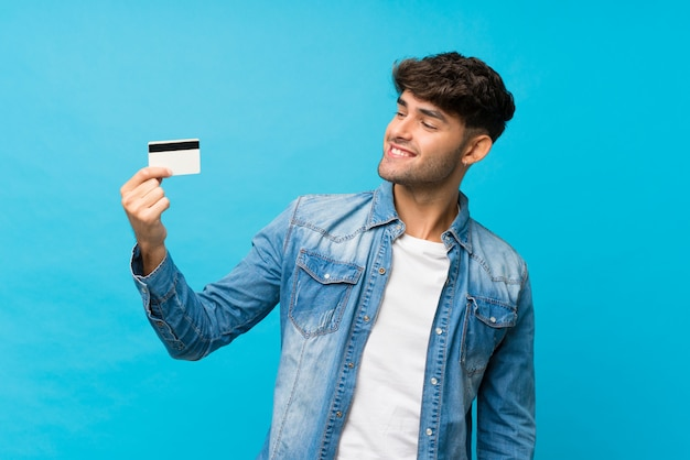 クレジットカードを保持している分離の青い壁の上の若いハンサムな男 Premium写真