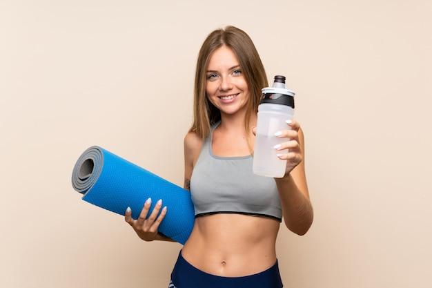 スポーツウォーターボトルとマットの隔離された壁の上の若い金髪スポーツ少女 Premium写真