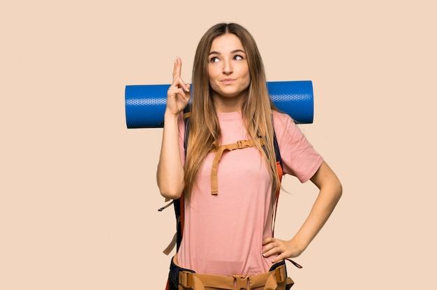 指を交差し、孤立した黄色の壁に最高を望む若いバックパッカーの女性 Premium写真