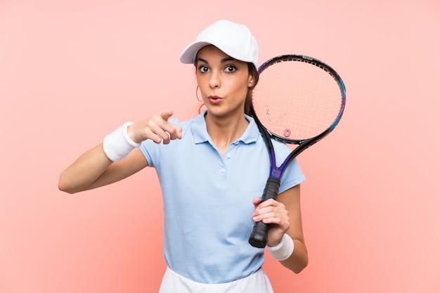 孤立したピンクの壁の上の若いテニスプレーヤー女性驚いて、フロントを指す Premium写真