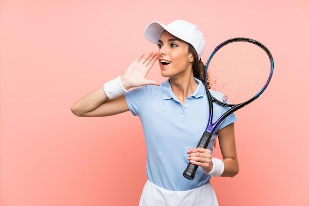 口を大きく開けて叫んで分離のピンクの壁の上の若いテニスプレーヤー女性 Premium写真