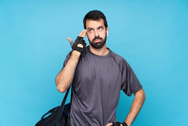 Молодой спортивный человек с бородой над синей стеной с проблемами, делая жест самоубийства Premium Фотографии