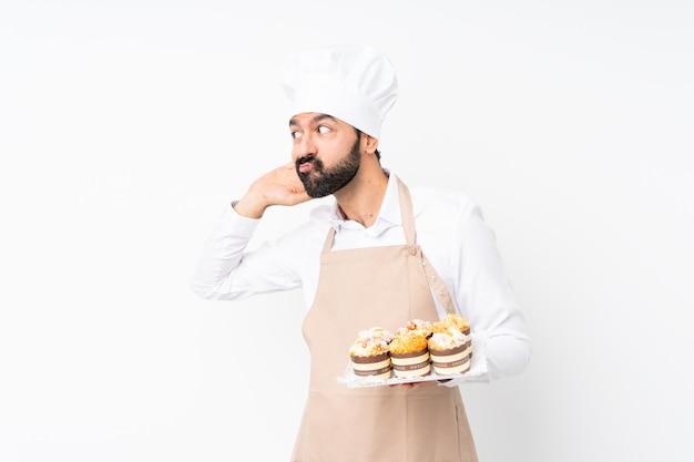 Молодой человек, держащий булочку над изолированной белой стеной Premium Фотографии