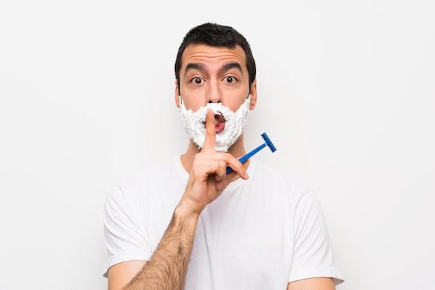 口に指を入れて沈黙ジェスチャーの兆候を示す分離の白い壁に彼のひげを剃る男 Premium写真