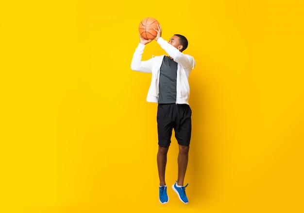孤立した黄色の背景の上のアフロアメリカンバスケットボールプレーヤー男 Premium写真