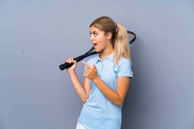 灰色の壁の上のティーンエイジャーのテニスプレーヤーの女の子が驚いて、側を指して Premium写真