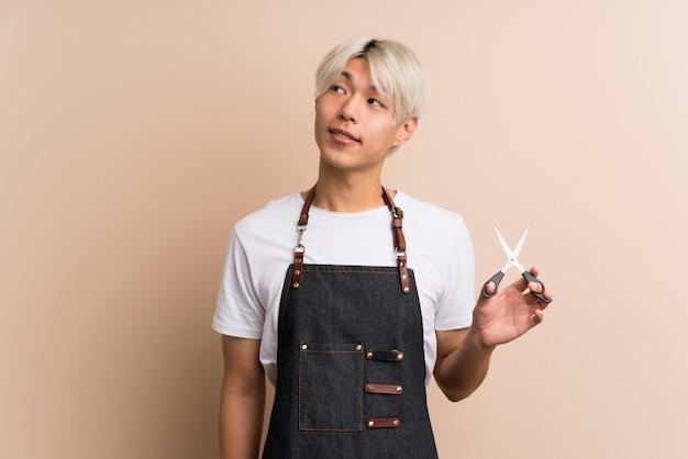 見上げる美容師や理髪店のドレスの若いアジア人 Premium写真
