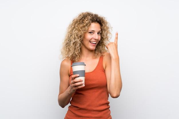 指を持ち上げながら解決策を実現するつもりのテイクアウェイコーヒーを保持している巻き毛の若いブロンドの女性 Premium写真
