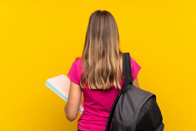 Молодая девушка студента над изолированным желтым цветом в заднем положении Premium Фотографии