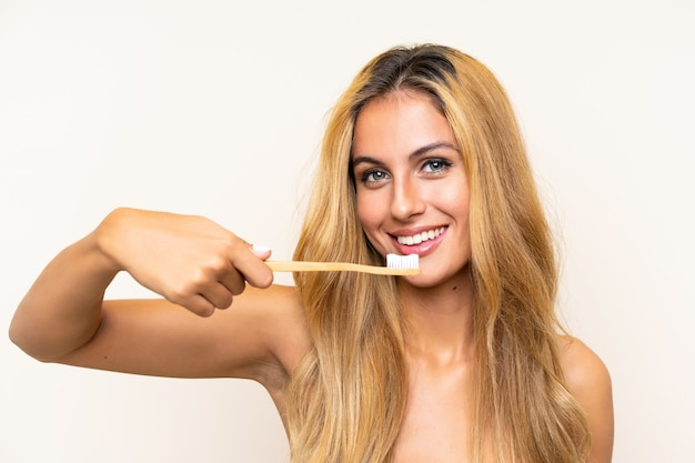 彼女の歯を磨く若いブロンドの女性 Premium写真
