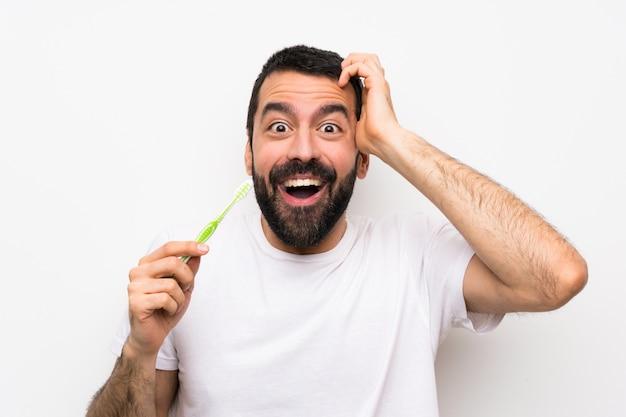 驚きのジェスチャーを作る分離白で歯を磨くひげを持つ男 Premium写真