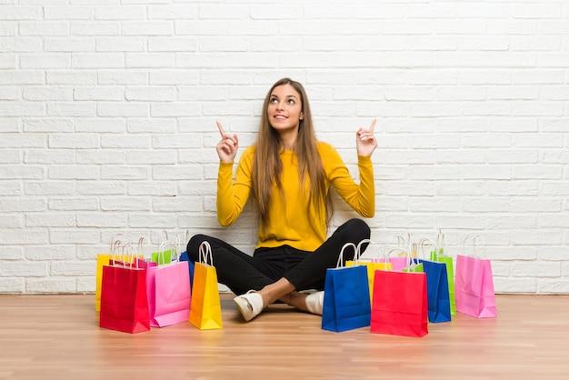人差し指で素晴らしいアイデアを指している買い物袋の多くを持つ若い女の子 Premium写真