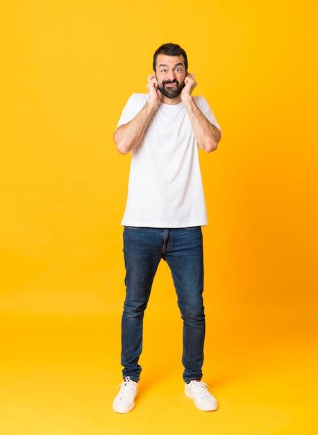 孤立した黄色いイライラし、耳を覆うひげを持つ男の全身ショット Premium写真