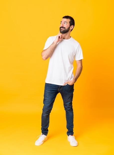 見上げながらアイデアを考えて分離された黄色の上のひげを持つ男の全身ショット Premium写真