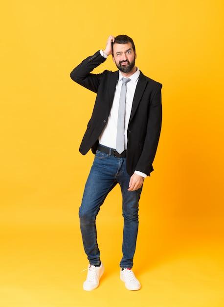 欲求不満の表現と分離された黄色でビジネスマンの全身ショット Premium写真