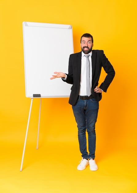 孤立した黄色の上のホワイトボードでプレゼンテーションを行う実業家の全身ショット Premium写真