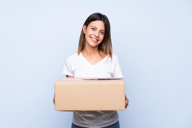 別のサイトに移動するボックスを保持している分離された青の上の若い女性 Premium写真
