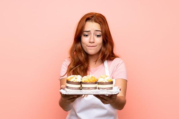 Рыжая девушка подросток держит много различных мини-пирожных за изолированный розовый Premium Фотографии