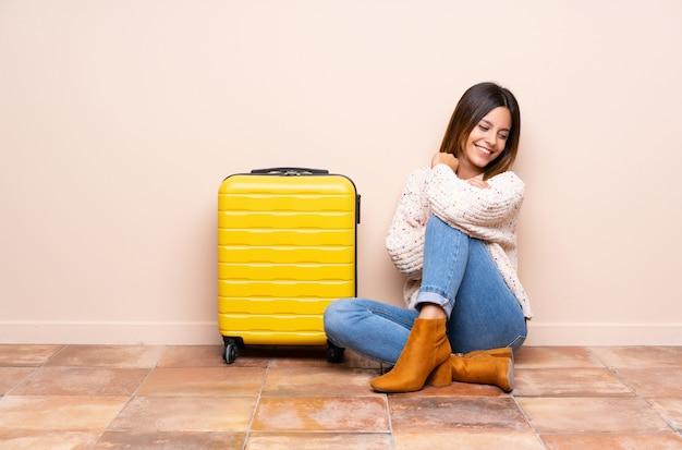 Путешественник женщина с чемоданом, сидя на полу от смеха Premium Фотографии