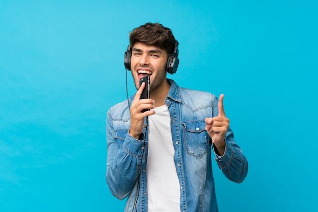 Молодой красавец над изолированной голубой с помощью мобильного телефона с наушниками и пения Premium Фотографии