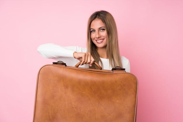 Молодая белокурая предпосылка женщины держа винтажный портфель Premium Фотографии