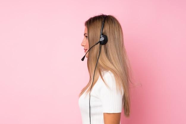 ヘッドセットを扱う若いブロンドの女性の背景 Premium写真