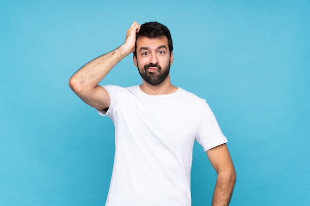 欲求不満と理解していない表情で分離された青の上のひげを持つ若者 Premium写真