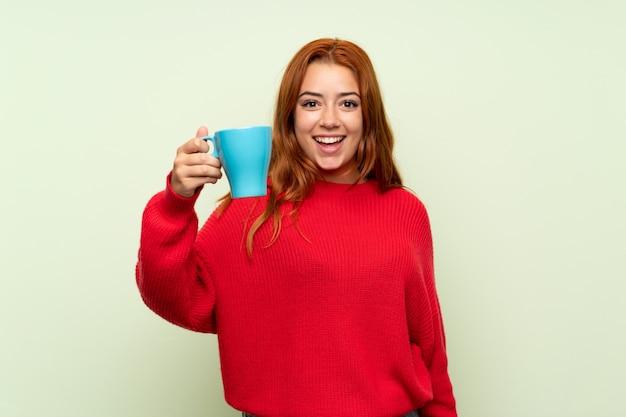 ホットカップのコーヒーを保持している分離された緑の上のセーターとティーンエイジャーの赤毛の女の子 Premium写真