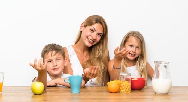 Мать с двумя детьми завтракает Premium Фотографии